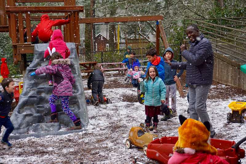 REVIEW PHOTO: CLAIRE HOLLEY - Massene Mboup, executive director of the International Leadership Academy in Lake Oswego, enjoys a snowy morning with students on Tuesday. 'When they come in the morning, the man who greets them is a black man. And hes the principal', says Mboup. 'At 4 or 5 years old, they see that it's possible that people of color can be this.'