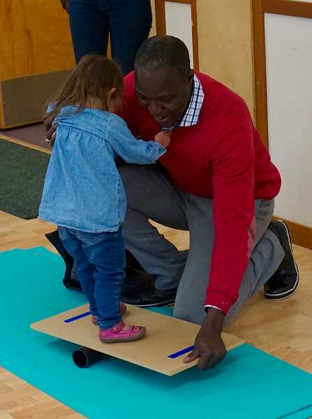 REVIEW PHOTO: CLAIRE HOLLEY - Massene Mboup helps a toddler try out a balance board at the International Leadership Academy in Lake Oswego.