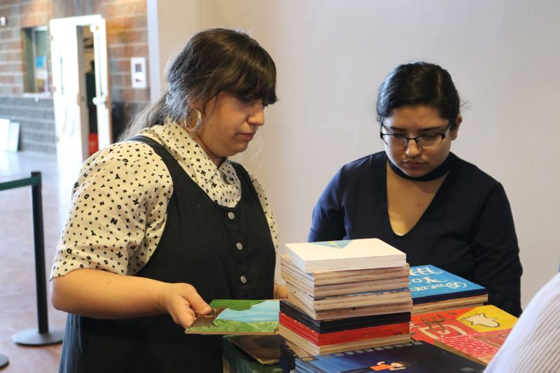 CONTRIBUTED PHOTO: REYNOLDS SCHOOL DISTRICT, DARYLN CHESTER - Art consultant Libby Werbell and student Itzel Gutierrez sort through student art, preparing for the March 8 auction.