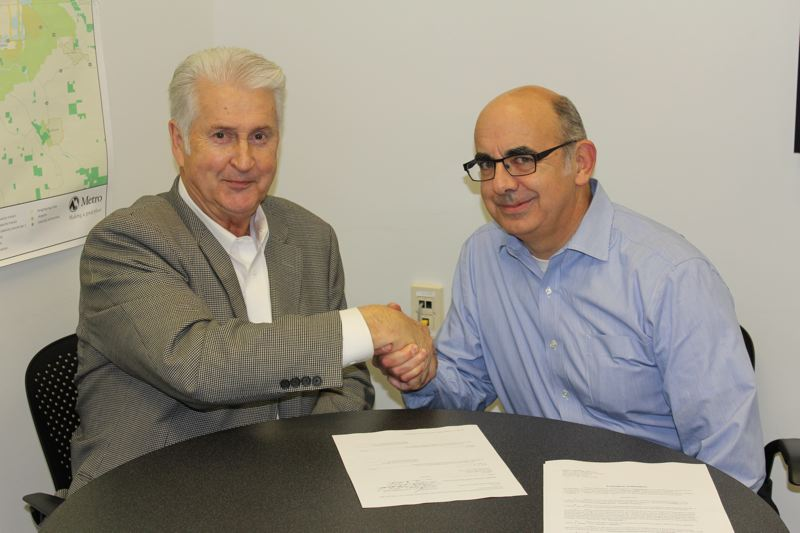 PHOTO COURTESY: METRO - George Heidgerken and Jim Desmond shake hands to finalize the signed agreement between the developer and Metro in 2014.