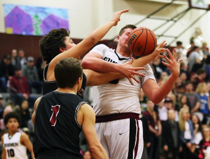 DAN BROOD - Tualatin juniors Caden Dickson (1) and Bridger Steppe battle Sherwood senior Jace Sucher for a loose ball during Thursday's game.