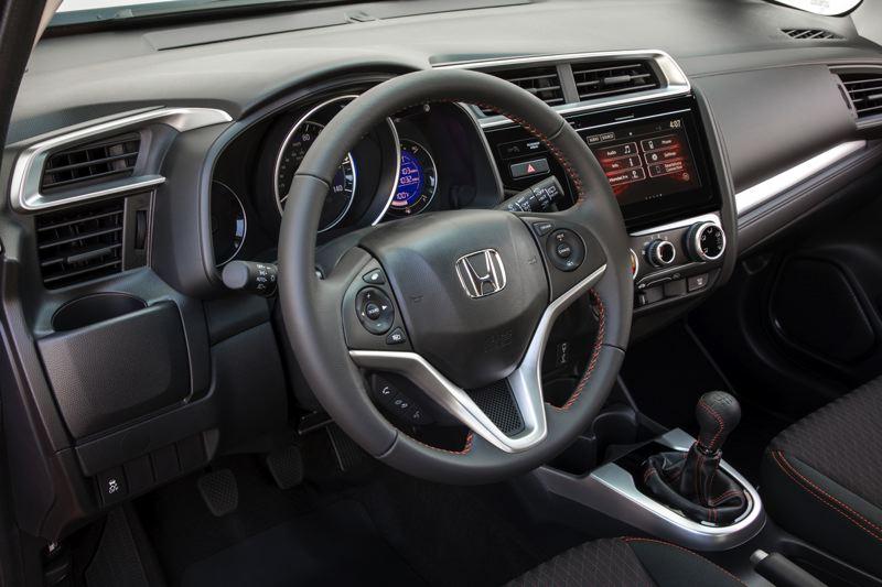 AMERICAN HONDA MOTOR COMPANY - The clean interior of the 2018 Honda Fit Sport is accented by orange stitching.