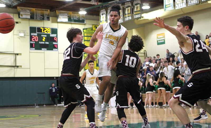 TIDINGS PHOTO: MILES VANCE - West Linn junior Damiko Tidmore makes a pass during his teams 62-51 home win over Sherwood on Friday night.