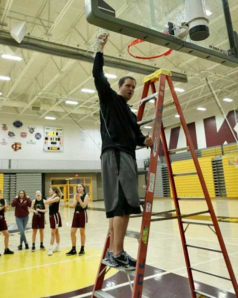 COURTESY PHOTO: VICKI VAN LOO PHOTOGRAPHY - Forest Grove head coach Dan Lumpkin cuts the remainder of the net from the FGHS gym during a celebratory ceremony Feb. 23 at Forest Grove High.
