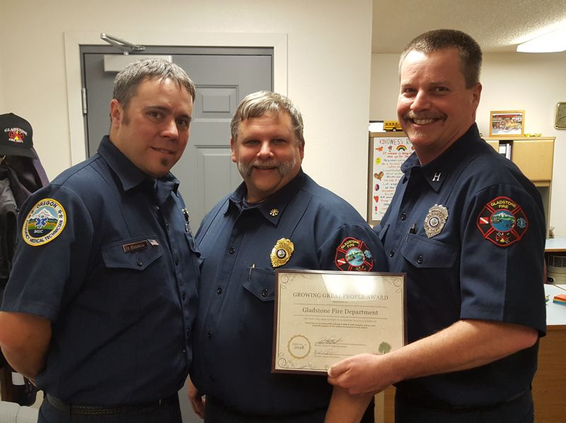 PHOTO COURTESY: LESLIE ROBINETTE - Gladstone fire officials Izaak Thoman, Mike Funk and Kirk Stempel accepted an award from the Gladstone School Board for their fire department's service to the communitys children.