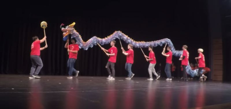 PHOTO COURTESY: LESLIE ROBINETTE - Gladstone High Chinese teacher Hao Li leads his students in a dragon dance performance in celebration of the Lunar New Year.