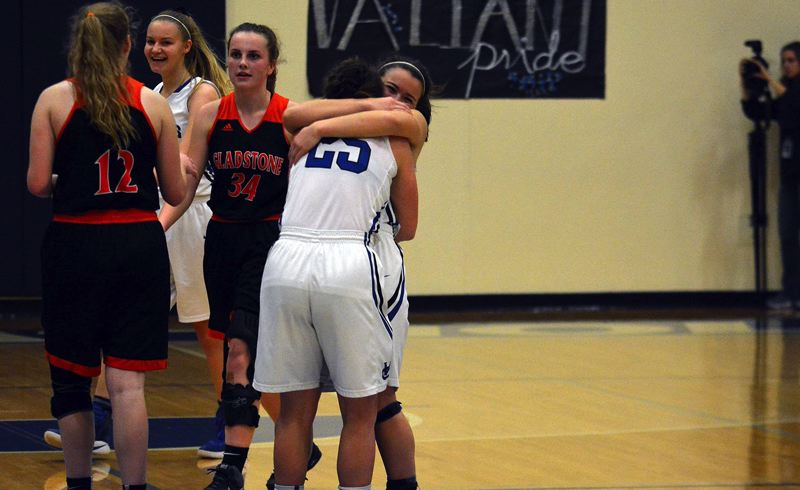 TIMES PHOTO: MATT SINGLEDECKER - Valley Catholic guards Callie Kawaguchi and Noelle Mannen celebrate their Class 4A play-in win over Gladstone.