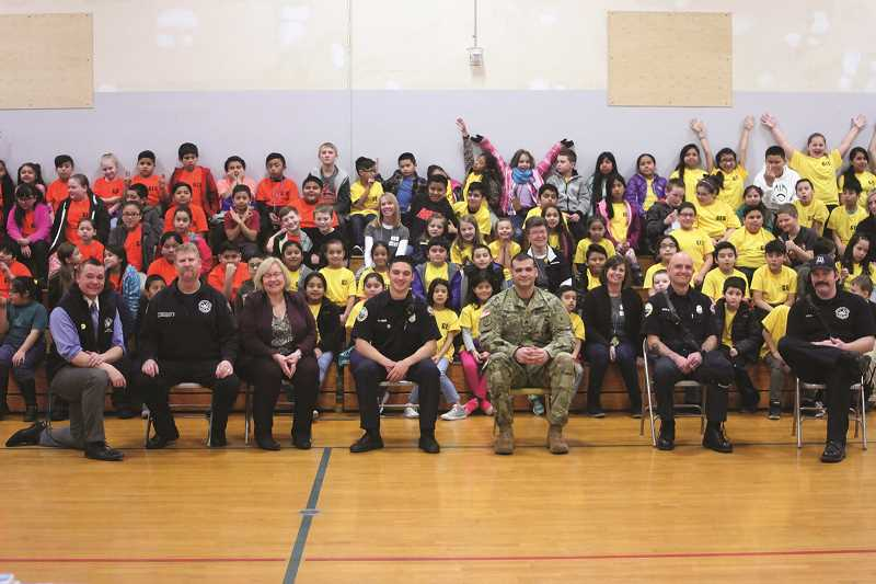 PHIL HAWKINS - Gervais Elementary School Principal Dr. Creighton Helms (left) kneels alongside (from left) Woodburn Fire District Lt. Robb Gramzow, Cindy Hunt of the Oregon Department of Education, WFD student firefighter Austin Amaya, Sgt. Mohamed Hussein of the U.S. Army, and WFD firefighters Ryan Johnson and Nick Ryan at the school's assembly celebrating its Operation Gratitude fundraiser last week.