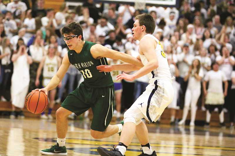 JO WHEAT - North Marion senior Andy Schmitz takes the ball up court in the Huskies' 58-57 loss to the No. 7 Henley Hornets on Friday. Schmitz was one of five seniors to finish their basketball careers on Friday, joining teammates Trevor Ensign, Bryce Lemon, Noah Vachter and Luis Nunez.