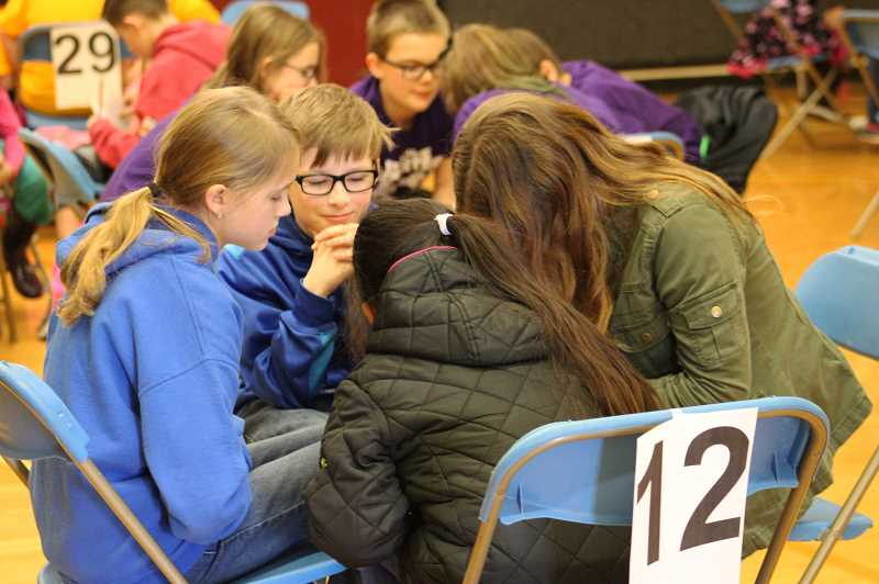HERALD PHOTO: KRISTEN WOHLERS - William White (center) and his teammates from Ninety-One School ponder their answers during the tournament on Feb. 22.