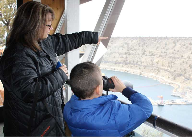 HOLLY M. GILL - Sherrie Reynolds, of Redmond, shows her son, Jacob  Serrano, nearly 7, where to focus his binoculars to see an eagle nest.