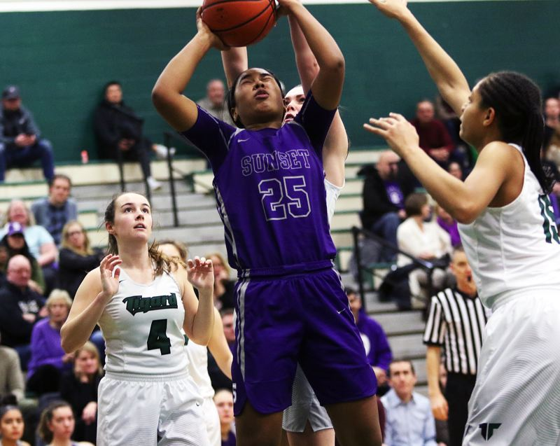 DAN BROOD - Sunset freshman Oby Nwokoma looks to go up to the basket during Tuesday's state playoff game at Tigard.
