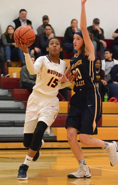 PAMPLIN MEDIA: DAVID BALL - Milwaukie guard India Gultry goes wide along the baseline for a three-point play against Hood Rivers Hannah McNerney in the Mustangs 35-33 win in the 5A qualifier game.