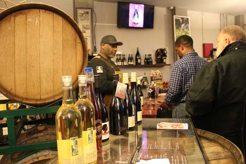 STAFF PHOTO: OLIVIA SINGER - Proprietor of Abbey Creek Vineyard & Winery Bertony Faustin pours glasses of his wine for guests to taste at his winery for the 'Local Story' event.