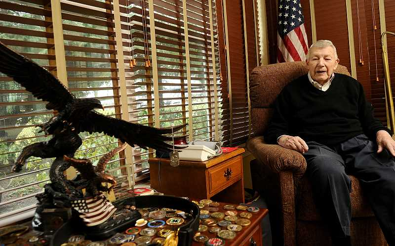 REVIEW PHOTO: VERN UYETAKE - Jim Thayer looks over the various awards and medals he received for military service and heroism.