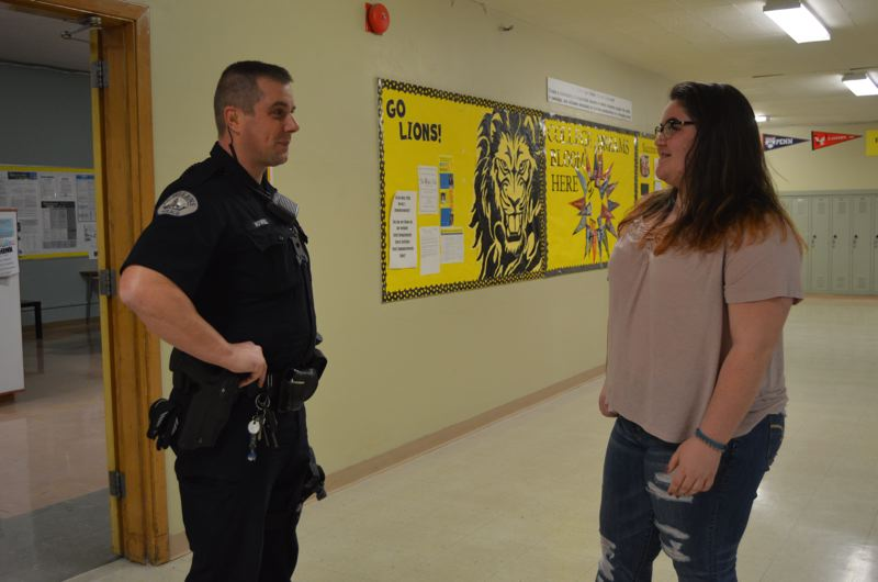 SPOTLIGHT PHOTO: NICOLE THILL - St. Helens Police Department School Resource Office Jeremy Howell chats with Kaycee Leanna, a sophomore, in the hallway of St. Helens High School on Wednesday, Feb. 28. Howell is assigned to the school district full-time and splits his days between district buildings as needed.