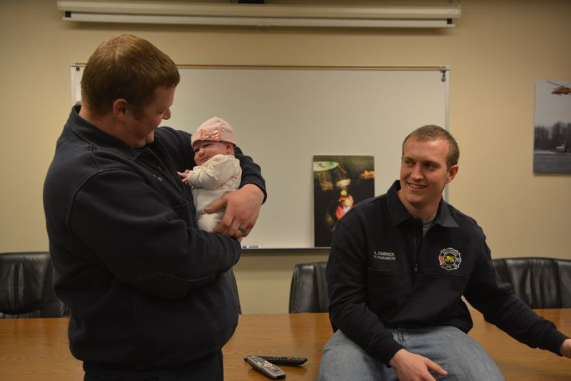 SPOTLIGHT PHOTO: COURTNEY VAUGHN - Justin Krieck (left) a firefighter/paramedic with Scappoose Fire District, and Austin Zimbrick, a firefighter/paramedic with Clatskanie Fire District, take turns holding Faith, a baby they helped deliver four weeks prior.