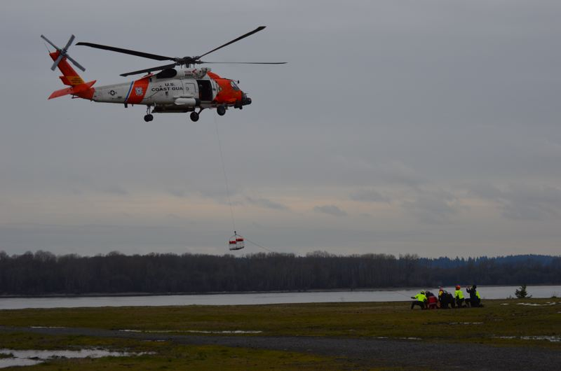 SPOTLIGHT PHOTO: COURTNEY VAUGHN - A U.S. Coast Guard helicopter from Astoria hovers over the St. Helens waterfront as fire and rescue crews from various agencies prepare to rush in for a basket hoist drill Friday, Feb. 23.