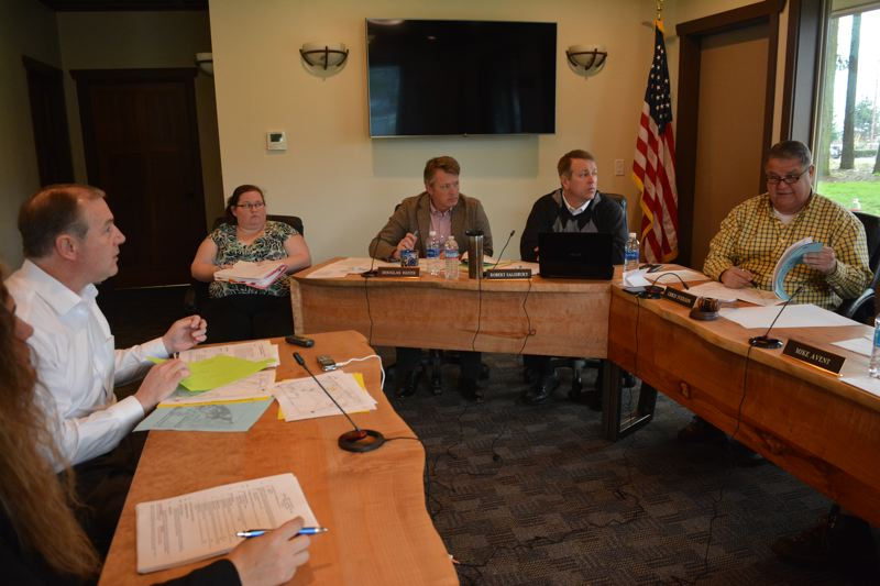 SPOTLIGHT PHOTO: COURTNEY VAUGHN - Steven Fuhr (left) of Toucan Farms, corresponds with Port of St. Helens staff and Commissioner Chris Iverson (right) during a Port of St. Helens meeting Feb. 14. Two weeks later, commissioners opted not to sell property to Toucan Farms.