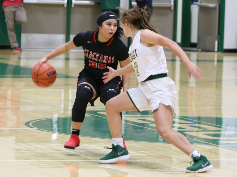 REVIEW/NEWS PHOTO: JIM BESEDA - Clackamas' Bri Phiakhamngon, working against Jesuit's Callan Harrington, finished with 10 points in the Cavaliers' 37-32 playoff win Friday over the Crusaders.