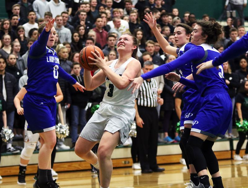 DAN BROOD - Tigard sophomore Campbell Gray goes to the basket between three Grants Pass defenders during the third quarter of Friday's state playoff game.