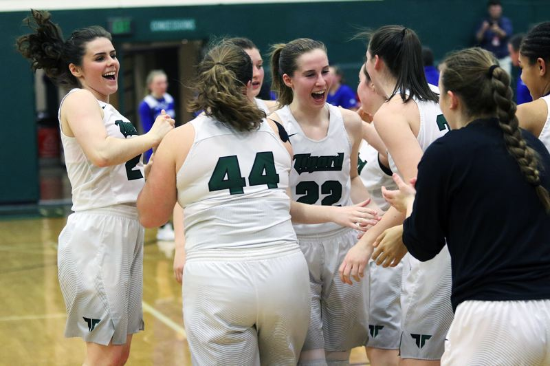 DAN BROOD - Tigard players celebrate at the end of their 51-48 state playoff victory over Grants Pass on Friday.