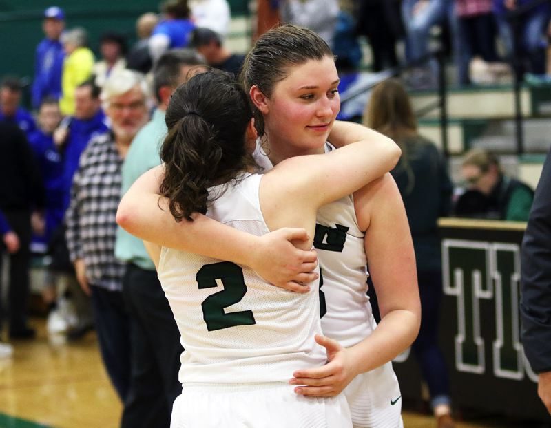 DAN BROOD - Tigard sophomore Kennedy Brown (2) and junior Campbell Gray share a hug following the 51-48 state playoff win over Grants Pass.