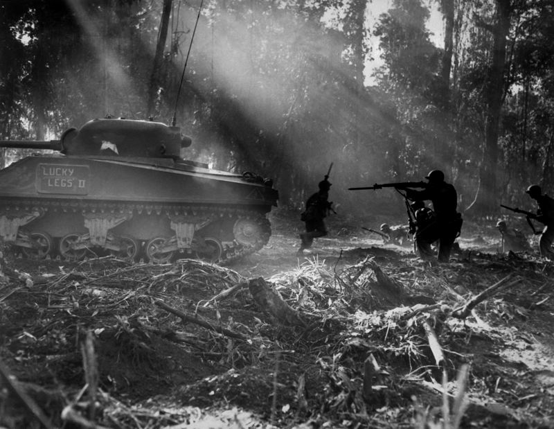 NATIONAL ARCHIVES AND RECORDS ADMINISTRATION - U.S. Army soldiers on Bougainville (one of the Solomon Islands) in World War II. Japanese forces tried infiltrating the U.S. lines at night; at dawn, the U.S. soldiers would clear them out. In this picture, infantrymen are advancing in the cover of an M4 Sherman tank.