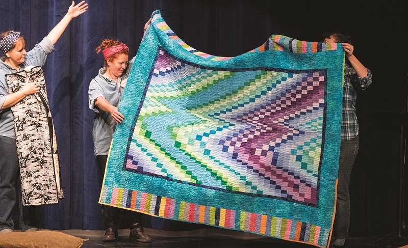 LON AUSTIN/CENTRAL OREGONIAN - Renee Moss, left, Heather Fraser and Lexie Tombleson display a quilt during the live auction just before intermission.