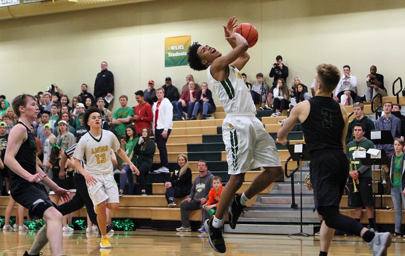 TIDINGS PHOTO: MILES VANCE - West Linn sophomore Micah Garrett gets fouled on a drive during his team's 72-62 home loss to West Salem in the second round of the Class 6A state playoffs on Saturday.