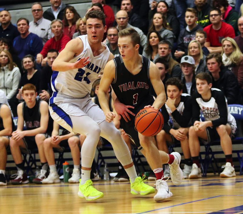 DAN BROOD - Tualatin junior Caden Dickson (right) drives past McNary's Ricardo Gardelli during Saturday's state playoff game.
