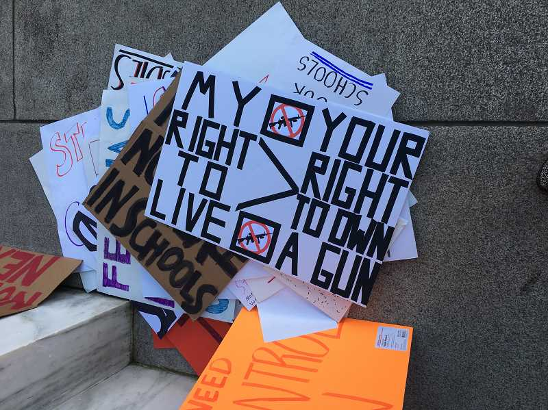 REVIEW PHOTO: CLAIRE HOLLEY - Students carried a variety of signs during their rally Monday in Salem, where they urged lawmakers to tighten gun laws and improve school safety.
