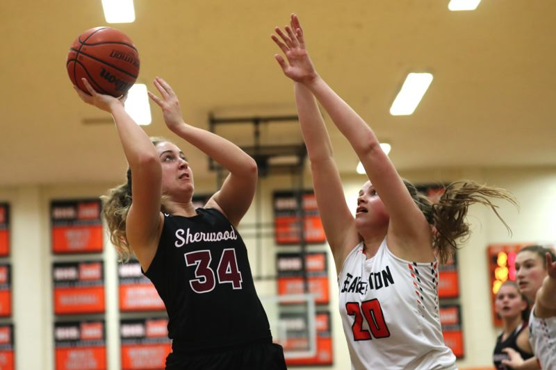 JAIME VALDEZ - Sherwood junior post Cali Etherington (left) looks to shoot over Beaverton sophomore Laura Erikstrup.
