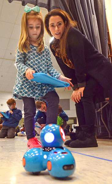 SPOKESMAN PHOTO: VERN UYETAKE  - Colleen Savelsbergh and her daughter, Charlotte, work to guide the robot through a maze.