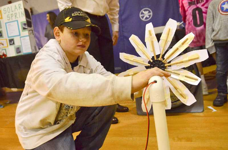 SPOKESMAN PHOTO: VERN UYETAKE  - Caleb Barber tries out his windmill to see how much electricity it will generate.