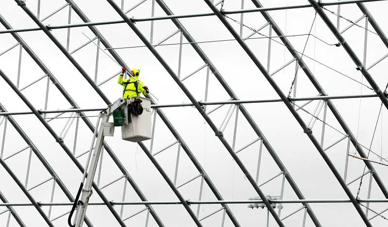 GARY ALLEN - A construction worker uses a cherry picker to access the tubular-steel framework of the indoor tennis facility George Fox University is erecting on the south side of Austin Sports Complex along Crestview Drive. The project is scheduled for completion in July.