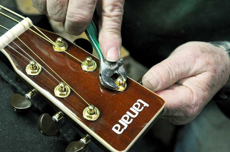 GARY ALLEN - GD Armstrong fixes hardware on a guitar at his shop in the mountains west of Yamhill.