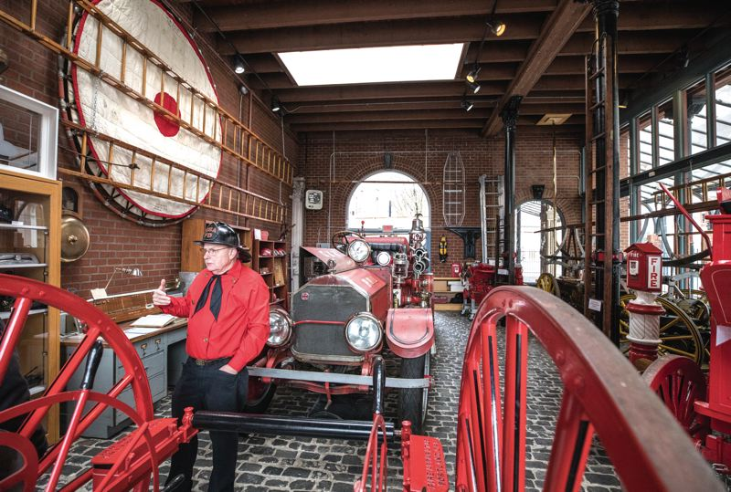 PORTLAND TRIBUNE: JONATHAN HOUSE - Retired Portland deputy fire chief Dave Short stands in front of a driveable 1917 American LaFrance Engine at the reopened downtown fire museum. Other historic items inlcude log books (top insert) and steam-powered equipment.