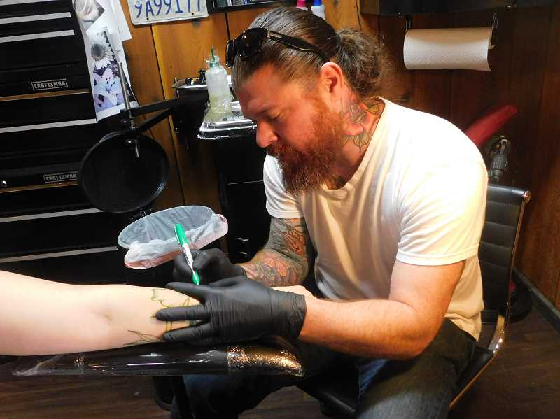 ESTACADA NEWS PHOTO: EMILY LINDSTRAND - When working on larger tattoos, Ellzey typically creates the design in permanent marker prior to using the tattoo machine.