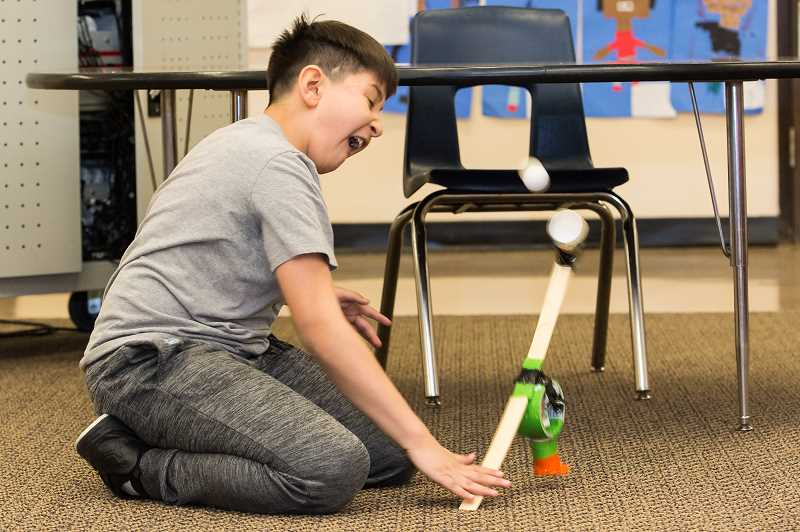 STAFF PHOTO: CHRISTOPHER OERTELL - Isaiah Lopez, 10, slaps at a contraption that he and his classmates built to propel a ping-pong ball into the air during an Intel volunteering event at W.L. Henry Elementary, March 2.