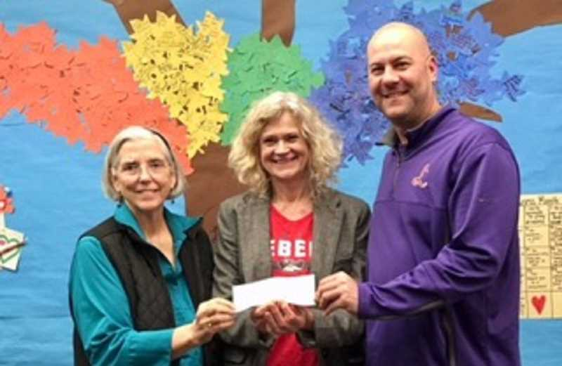 Rosalie Brown Lundh and Principal Jarvis Gomes of Deer Creek Elementary receive a check from Barbara Mills of the Beta Beta Chapter of Delta Kappa Gamma.