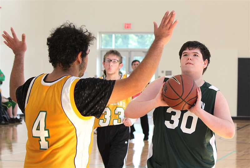 REVIEW PHOTO: SAM STITES - Connor Tiffany (right) prepares to shoot the ball after receiving a pass from his brother Dylan at the Special Olympics Oregon Northern Division Unified Basketball tournament on Saturday in Wilsonville.