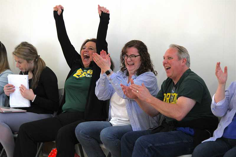 REVIEW PHOTO: SAM STITES - West Linn High School learning specialist Julie Holson celebrates a basket Saturday with West Linn fans Nicole and Rob Mitchell.