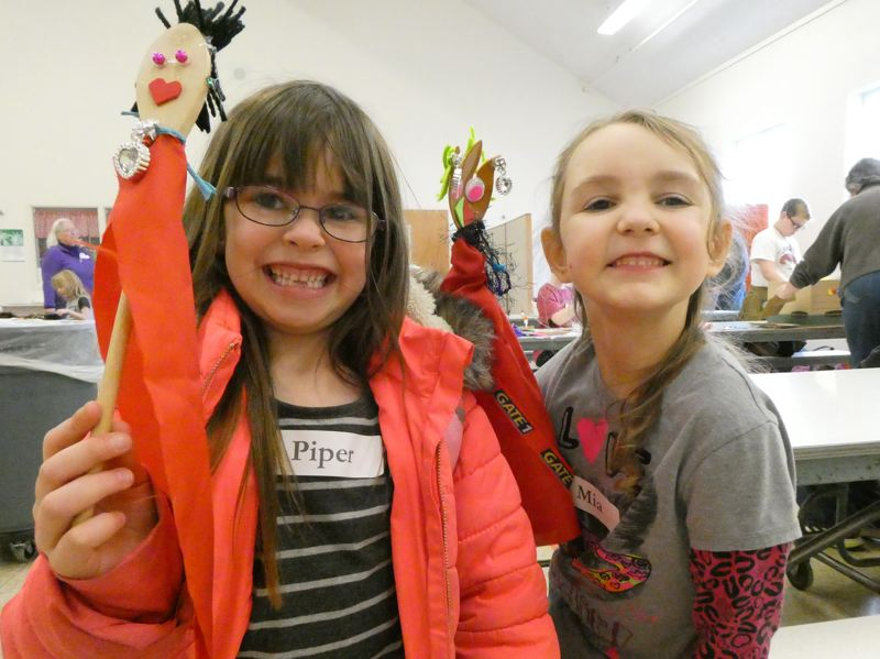 PHOTO COURTESY OF CHIP GARDES - Piper Burgard and Mia Crawford hold up puppets they made during the afterschool workshop offered by the Columbia City Community Library. Library volunteers obtained grant funding from the Columbia County Cultural Commission to help pay for supplies.
