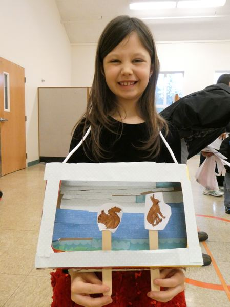 PHOTO COURTESY OF CHIP GARDES - Evelynn Worlitz displays a mini puppet theater she made during the workshop. Students were asked to make small theaters that could be worn around their necks with small puppets on Popsicle sticks poking through the bottom of the box.