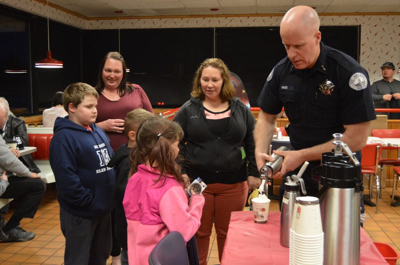 SPOTLIGHT PHOTO: NICOLE THILL - St. Helens Police Chief Terry Moss, right, helps serve cups of hot chocolate at a Cocoa with a Cop event hosted at the St. Helens Burgerville on Wednesday, March 7. Pictured with Moss are 9-year-old Christopher Grubb, 8-year-old Bryan Claussen, and 7-year-old MacKenzie Claussen who wait patiently for Moss to pipe out dollops on whipped cream on their cocoa.