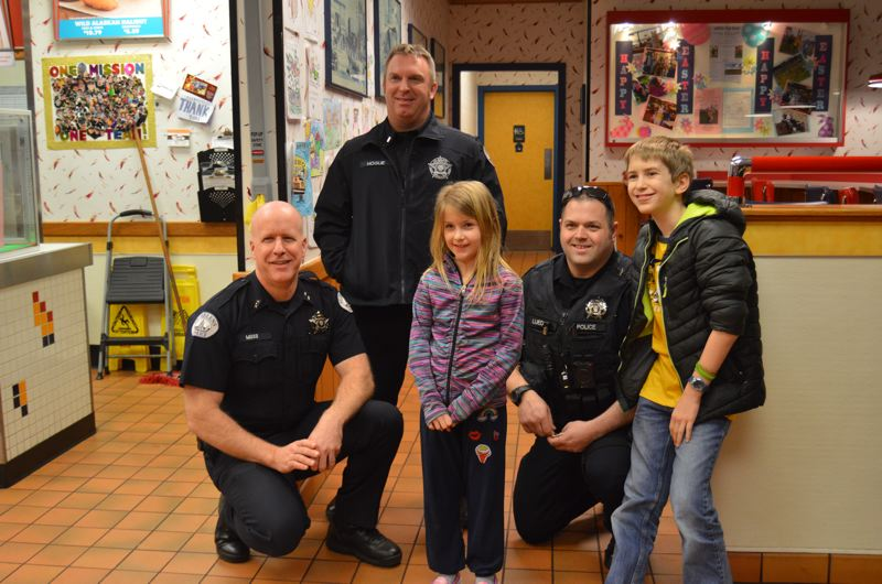 SPOTLIGHT PHOTO: NICOLE THILL - SHPD officers Terry Moss, Joe Hogue and Seann Luedke pose for a photo with Robby Schaffer, 11, and Ellie Schaffer, 7. In addition to hot cocoa, officers also handed out police badge stickers and specially designed trading cards with officers names and faces on them.