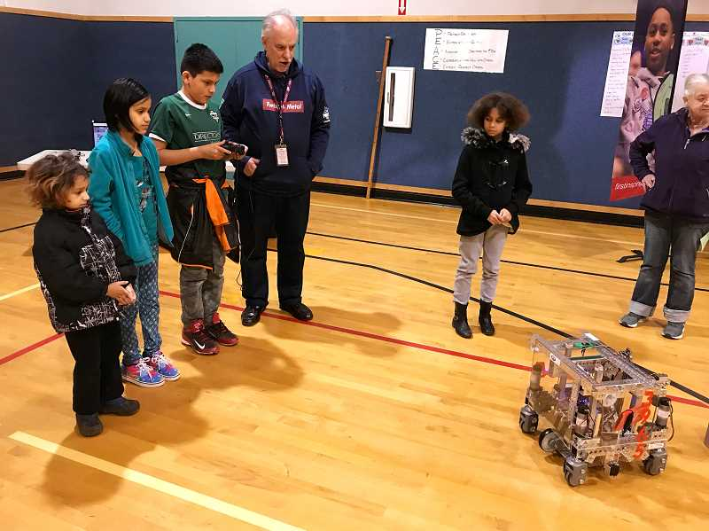 COURTESY OF DURHAM ELEMENTARY - Mr. Hancock, coach of the Tigard High School Tech Team (which is named 3965 Twisted Metal), shows Julio, a fifth-grader, the ropes in working a robot.
