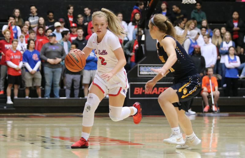 PAMPLIN MEDIA: JIM BESEDA - La Salle Prep's Emily Niebergall pushes the ball up the floor as Bend's Sydney Gardner brings defensive pressure during the first half of Thursday's OSAA 5A girls' basketball semifinal game.