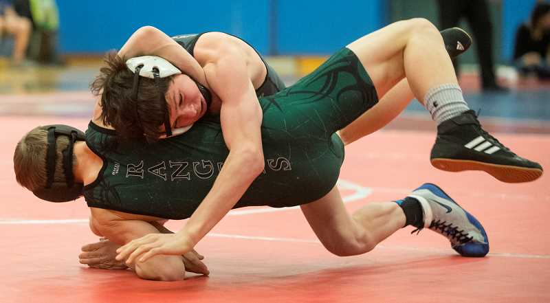 LON AUSTIN/CENTRAL OREGONIAN - Hunter Mode takes down an opponent from Estacada during a dual meet late in the season. Mode went on to win the regional and then state championships at 106 pounds. Mode is one of nine returning Cowboys who placed at this year's state meet.
